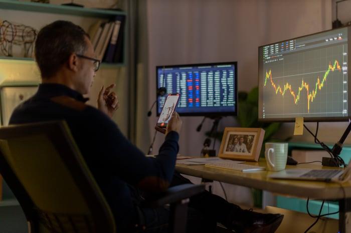 Monitoring trading at charts at a home office.