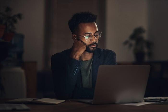 Un homme à son ordinateur portable dans une profonde réflexion.