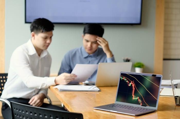 Un ordinateur portable affichant un graphique boursier en baisse avec deux personnes regardant un document en arrière-plan.