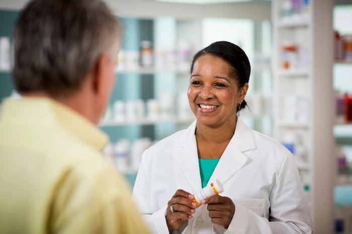 Un pharmacien souriant tenant une bouteille d'ordonnance et parlant avec un client.
