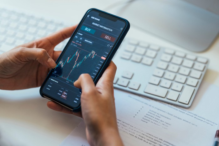 A person holding a smartphone that's displaying a volatile stock chart with buy and sell buttons.