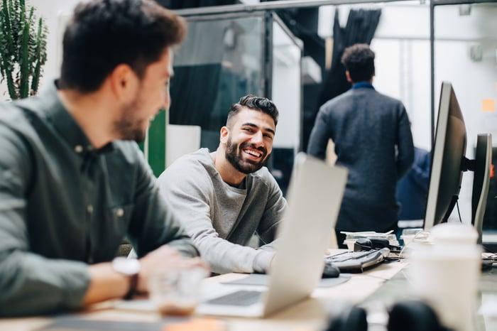 Un collègue assis souriant à un autre devant son ordinateur dans son espace de travail.