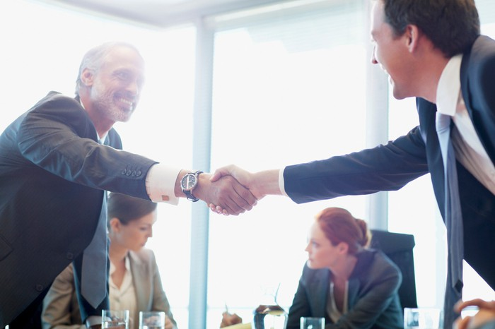 Businessmen shaking hands in a conference room.