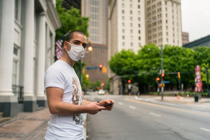 Person wearing a mask, holding a phone and standing on the side of the road.