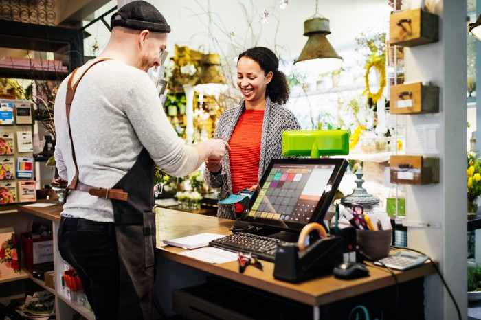 Une femme paie dans un magasin à un homme derrière un comptoir.