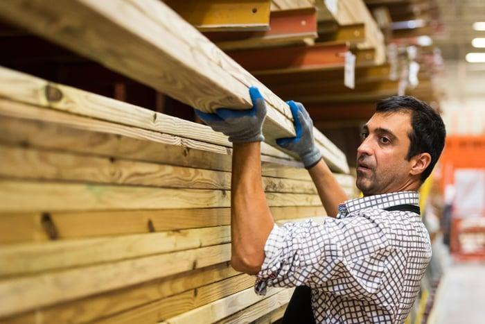Man stacking lumber at store