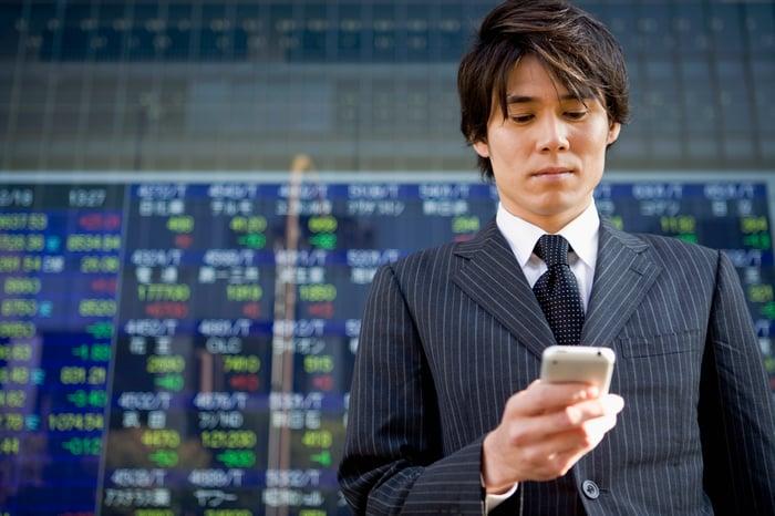 Homme d'affaires vérifiant son téléphone devant un tableau des stocks.
