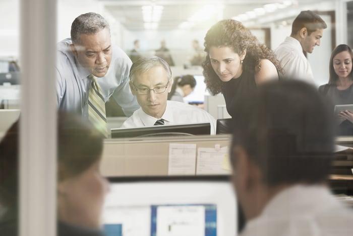 Les gens se pressent autour d'un ordinateur.