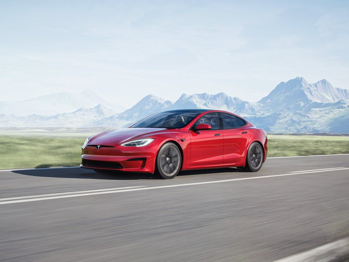 A red Tesla Model S driving along a highway with a backdrop of hazy, sunlit mountains.