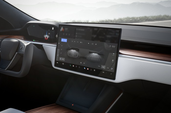 View of the display panel of a Tesla Model S electric vehicle, seen from the passenger seat.  The instrument panel, steering wheel and display panel are all visible.