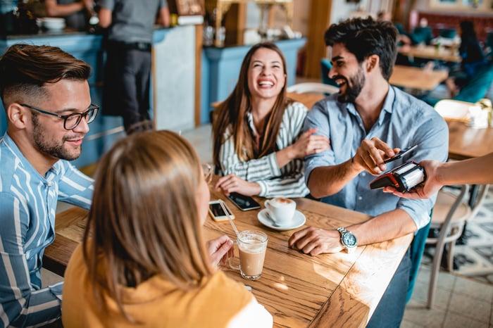 Un groupe de personnes assises à une table dans un restaurant avec une personne payant avec un téléphone portable.