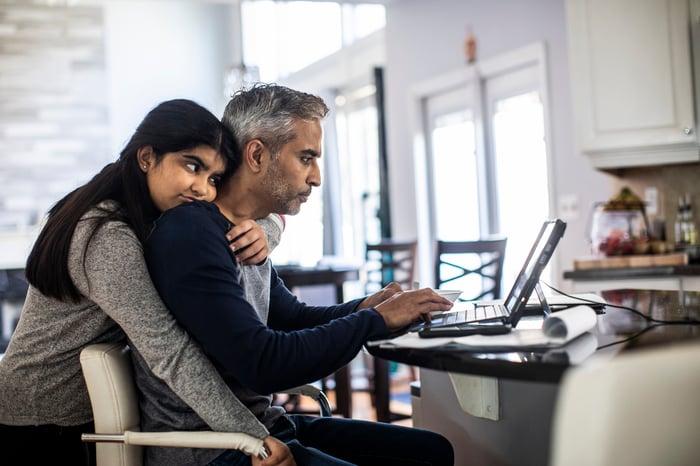 Un homme utilisant un ordinateur avec une fille le serrant dans ses bras par derrière.