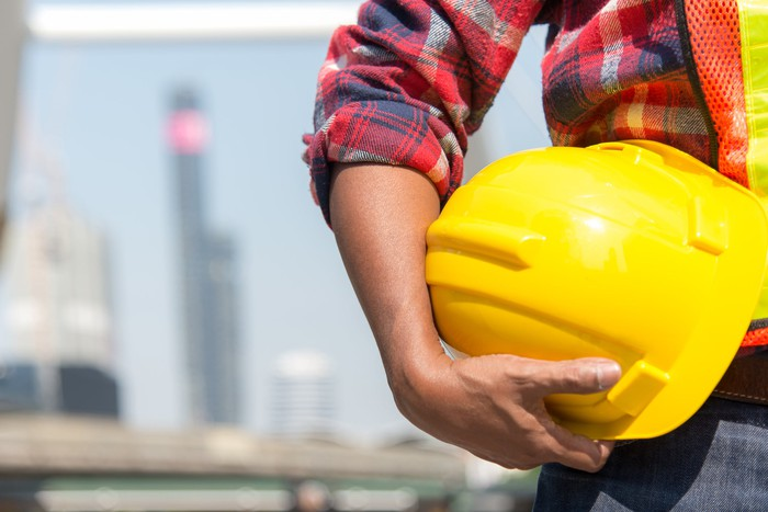 A construction worker holds a yellow hard hat.