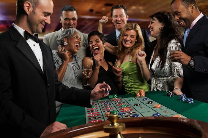 Un groupe de joueurs bien habillés joue à la roulette.