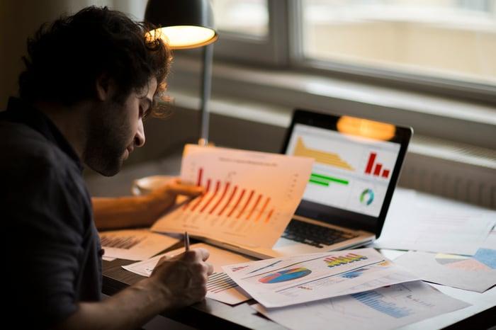 Investisseur étudiant divers tableaux et graphiques, à la fois sur papier et sur tablette numérique.