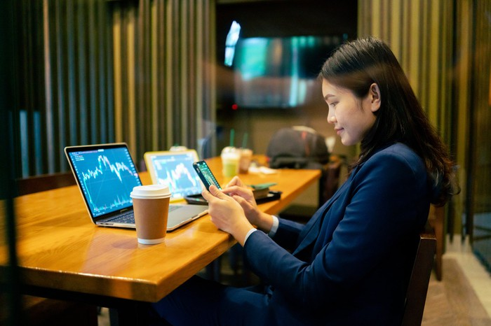 Trading cryptos on one's laptop and phone inside an office.