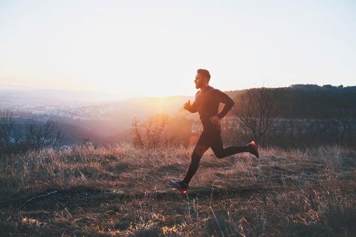 Courir le long d'une colline au lever du soleil.