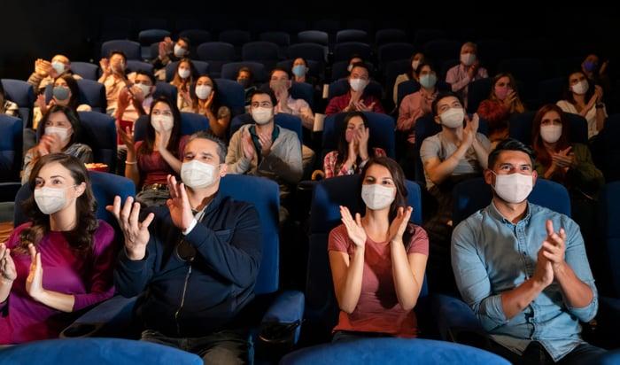 des cinéphiles masqués applaudissant dans un théâtre bondé.