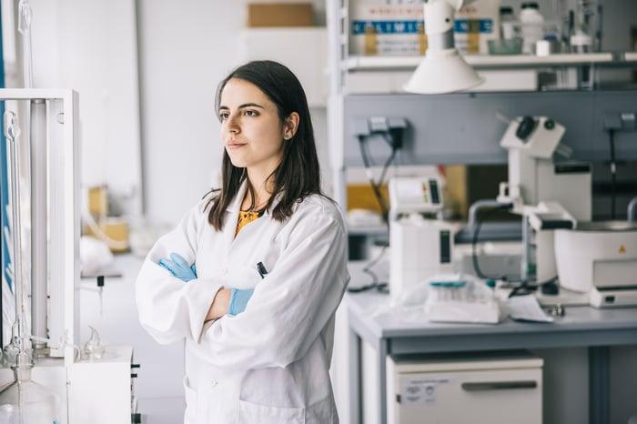 Un scientifique se tient dans son laboratoire, regardant loin de son banc tout en réfléchissant.