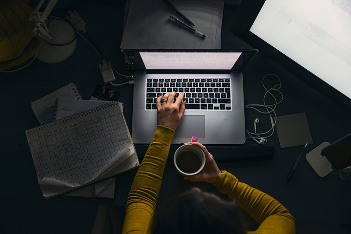 Person using a laptop while holding a mug.