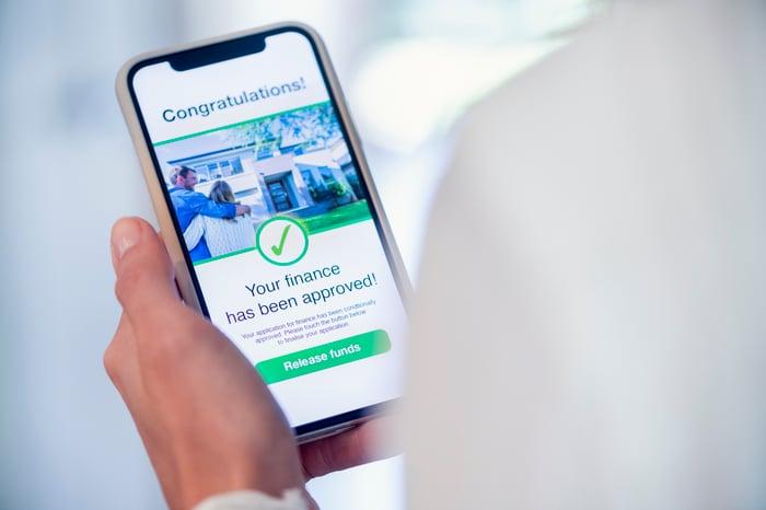 Personne visualisant l'approbation de prêt en ligne sur un téléphone mobile.
