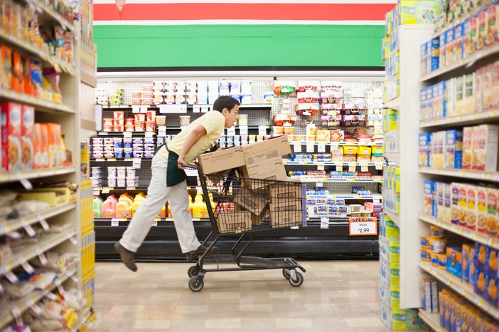 Grocery worker riding on a cart in a store.