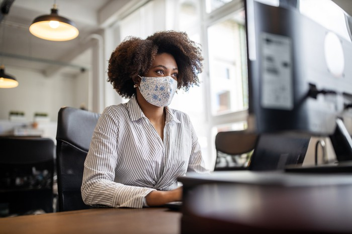 Business person sitting at a screen with a face covering.
