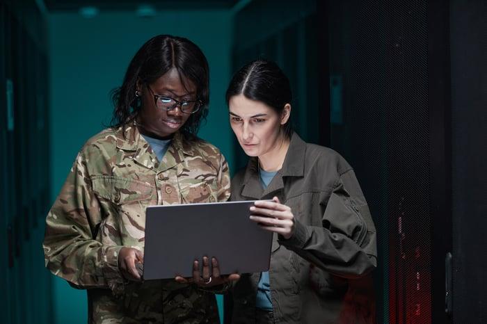 Deux personnes portant des treillis tenant un ordinateur portable.