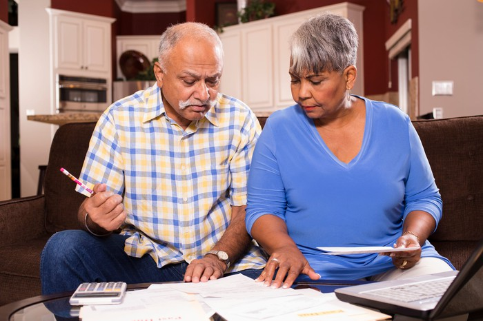 An elderly couple examines their finances and bills.