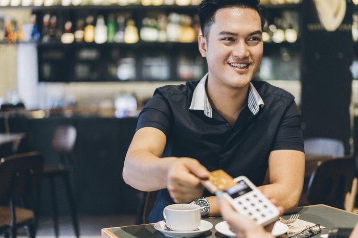 A person holding their credit card over a portable credit card reader in a coffee shop.