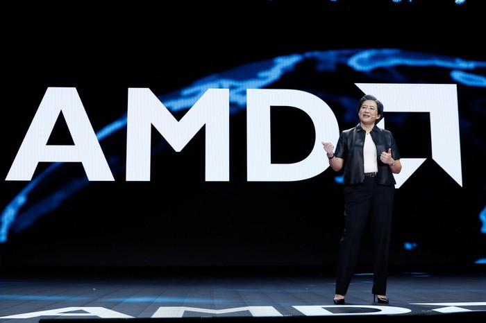 AMD CEO Dr. Lisa Su speaking on a stage with an AMD logo in the background.