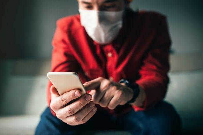 Une personne portant un masque facial touche l'écran de son téléphone.