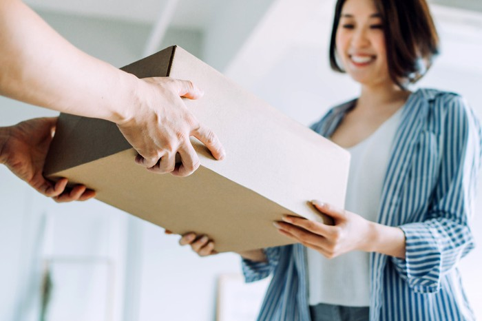 A woman receives an e-commerce package at her doorstep.