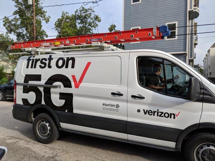 Un camion de service Verizon se trouve sur une route à l'extérieur de la maison de quelqu'un avec un chauffeur assis sur le siège du conducteur.