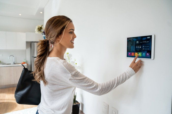 Woman interacting with a smart-home device.