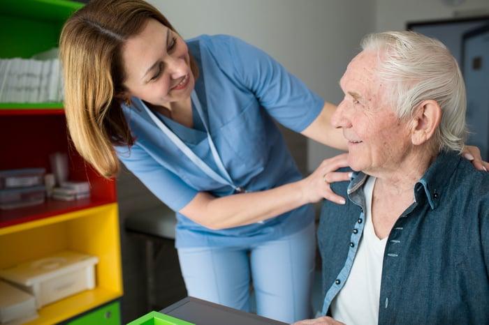 A nurse greeting an elderly man in his house.