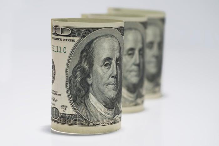 Trois billets de cent dollars s'enroulaient, se tenaient sur le côté et étaient bien rangés.