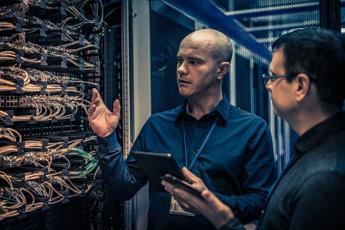 Deux personnes vérifient les serveurs cloud dans un centre de données.