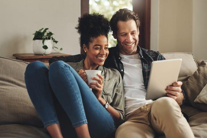 Couple sur le canapé naviguant en ligne.