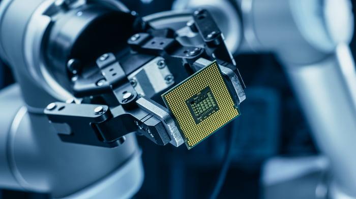 An advanced robot arm holding a computer processing chip.