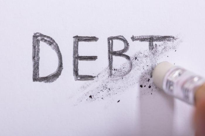 Une gomme effaçant le mot dette.