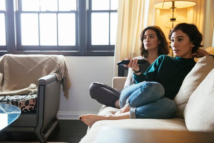Deux personnes assises sur un canapé regardent la télévision.