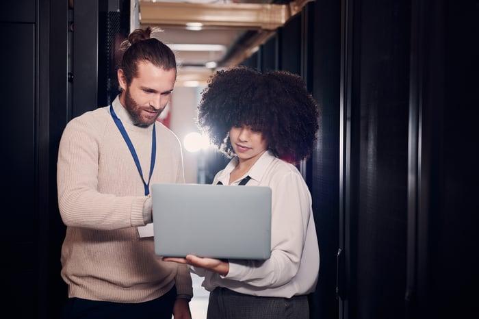 Deux personnes regardent un ordinateur portable dans un centre de données.