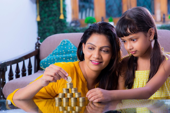 A mother and daughter making piles of coins on a table.