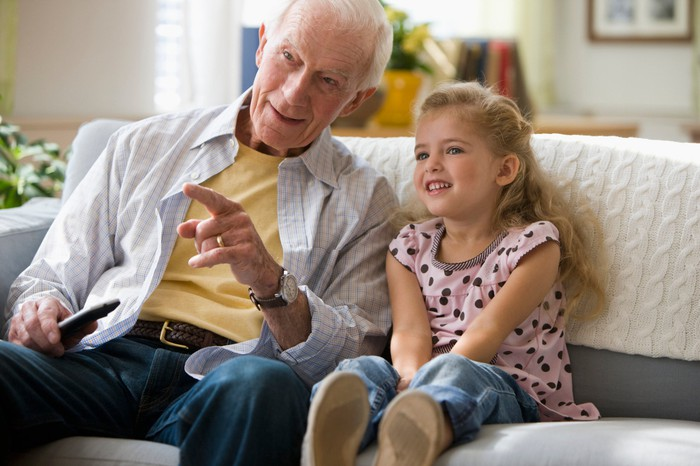 A grandfather holding a remote control and granddaughter sitting on a couch.