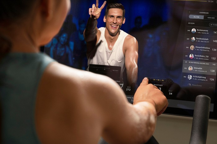 A person on a Peloton bike watching a streaming workout.