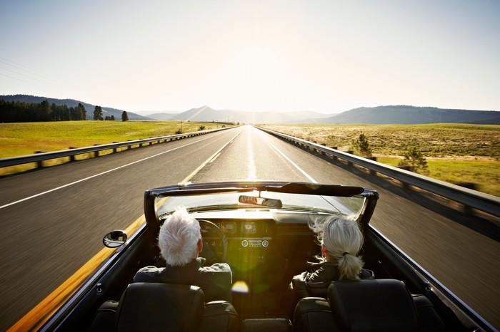 A white-haired couple driving down the road in a convertible with fields around them and mountains in the distance.