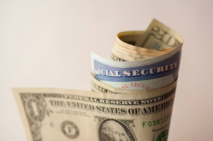 Social Security card wrapped in bills