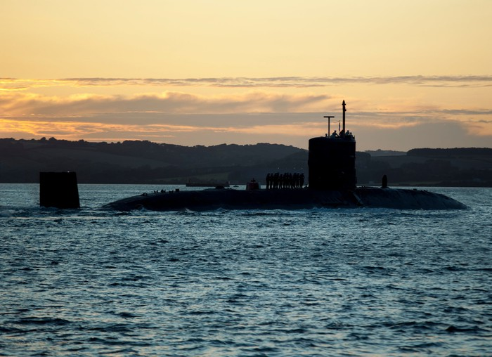 A submarine in the water at dusk.