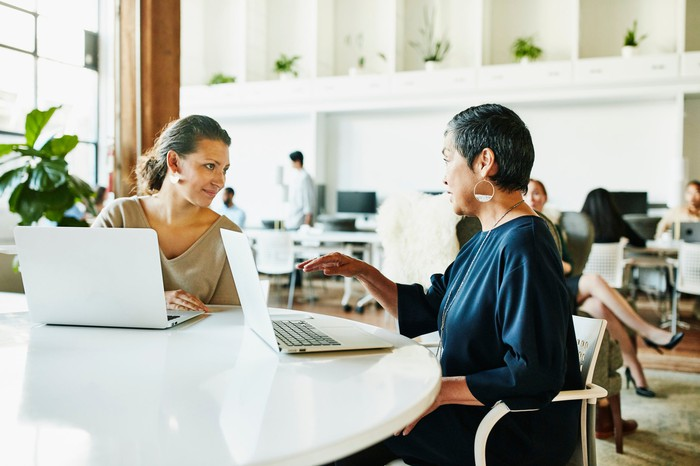 Deux personnes à table avec des ordinateurs portables.